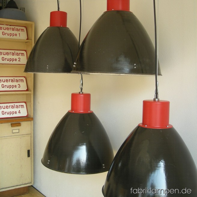 Impressive industrial lamps in black and red. Material: black enameled sheet and red painted top, with wire rope suspension. The lamps are cleaned and newly electrified, with E27 sockets. Total height: ca. 49 cm (19,3 inches). Diameter of the shade ca. 53 cm (21 inches).