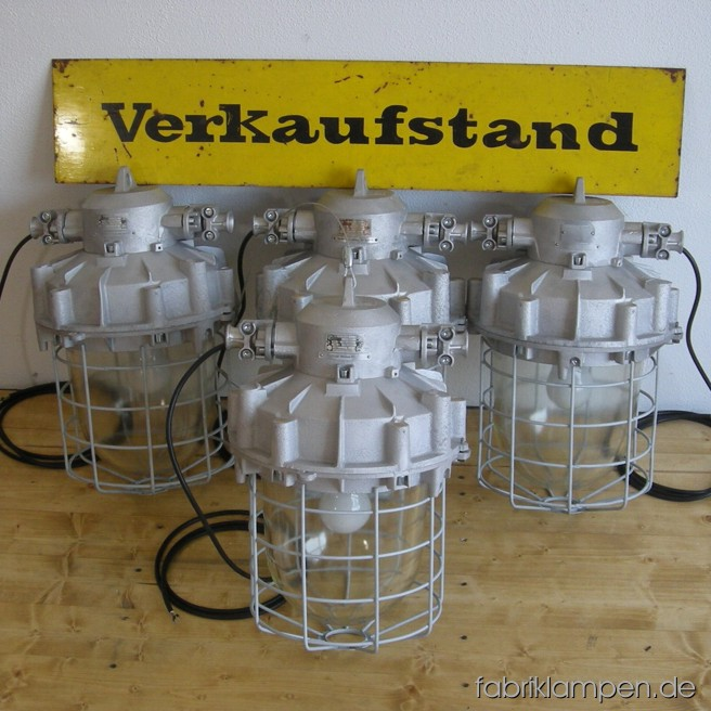Huge industrial bunker lamps. Material: aluminium, steel, glass. The lamps are renewed: cleaned, the safety grids are sandblasted and new galvanized; they are newly electrified, with ca. 2 m wire. Total height: ca. 55 cm (21,7 inches), weight ca. 14 kgs. The small bunker lamp on the last gallery picture is our benchmark: it is 38 cm (15 inches) height.