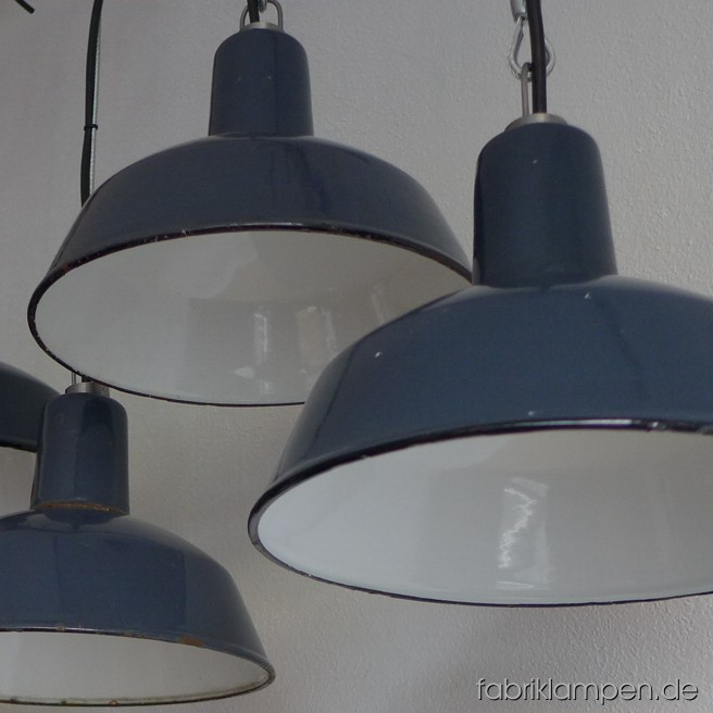 Small industrial lamps with black inscriptions. Material: blue (grayish) enameled sheet. Newly electrified, with wire-rope suspension. Height of the lamp is ca. 18 cm (7 inches), diameter of the shade is ca. 26 cm (10,2 inches).
