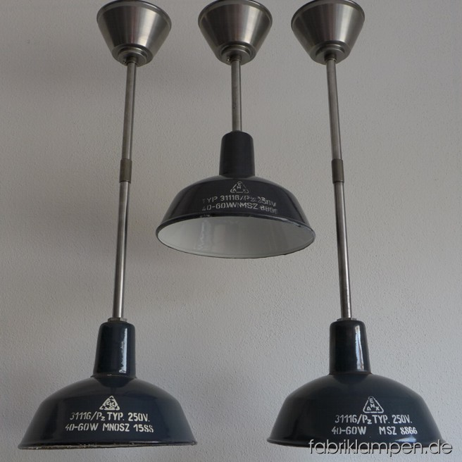 Nice small industrial lamps with inscription. Material: blue (some grayish) enameled sheet. Newly electrified, with steel-tube suspension and canopy. Height of the shade is ca. 18 cm (7 inches), diameter of the shade is ca. 26 cm (10,2 inches), total height of the Lamps between 45 and 74 cm (17,7 – 29,1 inches).
