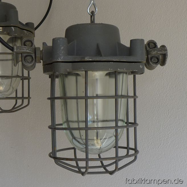 "Rare gray bunker lamps. Material: gray varnished casing, safety glass and grid.  Newly electrified, with E27 sockets. We have 4 pieces on stock. Height of the lamps ca. 30 cm (11,8 inches), diameter of the lamps (without ""ears"") ca. 20 cm (7,9 inches)."