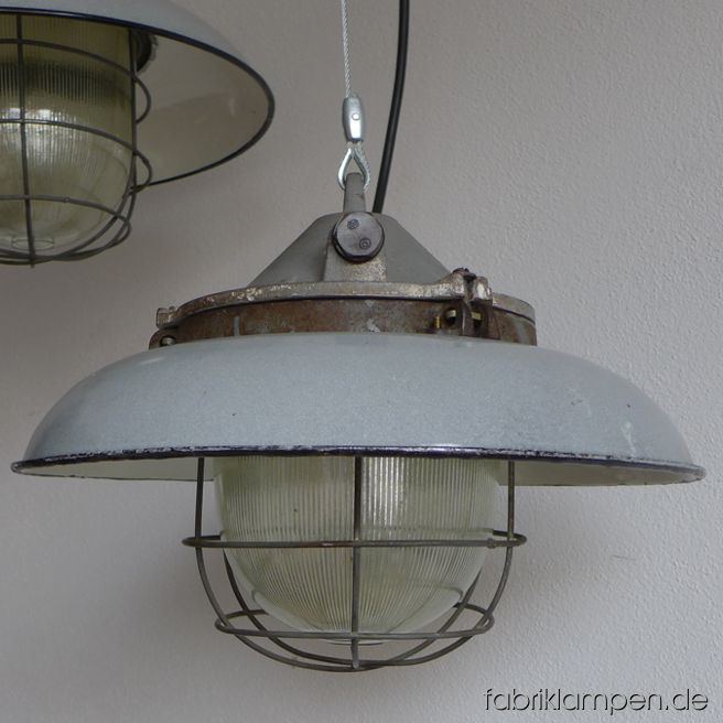 Rare gray bunker lamps with enameled shades. Material: gray enameled sheet, casted iron head. Newly electrified, with E27 sockets. We have 3 pieces on stock. Height of the lamps ca. 29 cm (11,4 inches), diameter of the shades ca. 41 cm (16,1 inches).