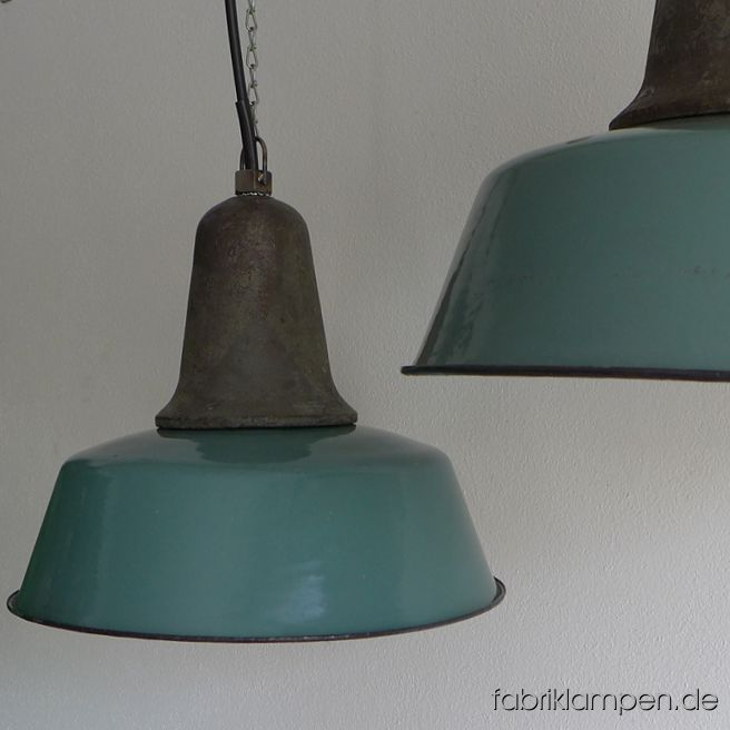Nice old factory lamp with green, blue or gray enameled shade. Material: enameled sheet, casted iron head. Newly electrified, with E27 sockets. Height of the lamps ca. 33 cm (13 inches), diameter of the shades ca. 41 cm (16,1 inches). The lamps will be shipped with 2 m cable and suspension eye (chain or steel-tube suspension is possible for an additional charge).