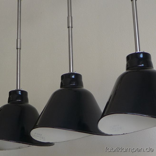 Rare old black enamel design factory lamp produced by VEB Leuchtenbau Leipzig (LBL). The asymmetric shades are elegant and functional over a long table, sideboard, bar or counter. The lamps have the typical traces of usage and age. Material: black (inside white) enameled steel sheet. Newly electrified, with E27 ceramic sockets. Height of the lamp ca. 26 cm (10,2 inches), width of the shade ca. 38,5 cm (15,2 inches), depth oft he sahe ca. 26 cm (10,2 inches). Total height with steel tube suspension and canopy 81 cm (32 inches). The lamps can be shipped also with suspension eye and cable (textile cable).