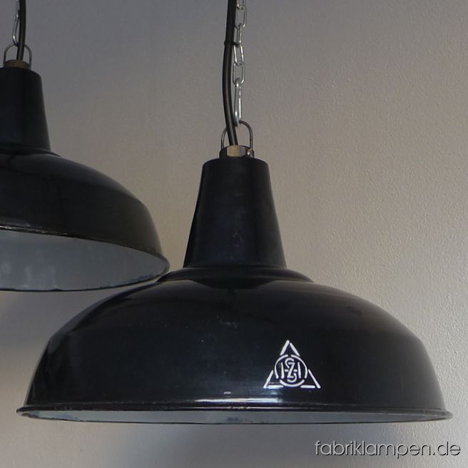 Very rare antique black industrial lamps with hallmark as pair. These old factory lamps have the traces of usage and age. Material: black (inside white) enameled steel sheet. Cleaned and newly electrified, with E27 ceramic bulbholders. Height of the lamps ca. 24,5 cm (9,6  inches), diameter of the shades ca. 40 cm (15,7 inches).