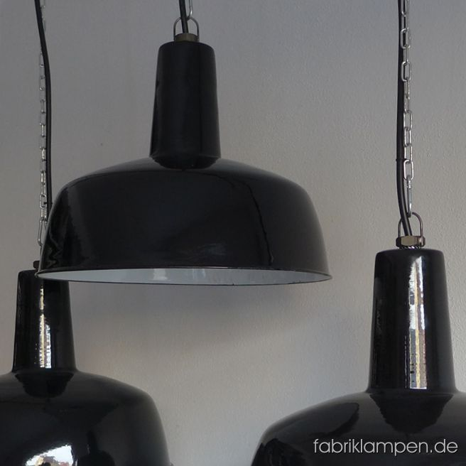 Rare antique black enamel lamps in classy form. These well preserved old factory lamps have the light traces of usage and age. Material: black (inside white) enameled steel sheet. Cleaned and newly electrified, with E27 ceramic bulbholders. Height of the lamps ca. 33 cm (13  inches), diameter of the shades ca. 41 cm (16,1 inches).