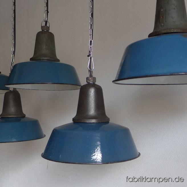Nice old blue factory lamp with blue enameled shade, mostly hallmarked. Material: enameled sheet, casted iron head. We have also a couple of lamps in other colours (like green or grayish green) in stock. With traces of age and usage. Cleaned, newly electrified, with E27 ceramic sockets. Height of the lamps ca. 24 cm (9,4 inches), diameter of the shades ca. 32 cm (12,6 inches). The lamps will be shipped with 2 m cable and suspension eye (chain or steel-tube suspension is possible for an additional charge).