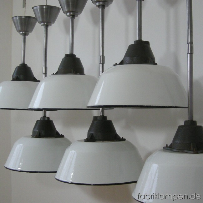 Industrial lamps with white enameled shades. Material: enameled sheet and casted iron, with iron suspension. Total height: as on the pictures: 74 cm (29,1 inches), with one steel tube 46,5 cm (18,3 inches). With another steel tube of 25 cm (9,8 inches) the total height can be increase up to 99 cm (39 inches). Height lamp ca. 23 cm (9 inches), diameter of the lamp ca. 36 cm (14,2 inches). 28 pieces available.