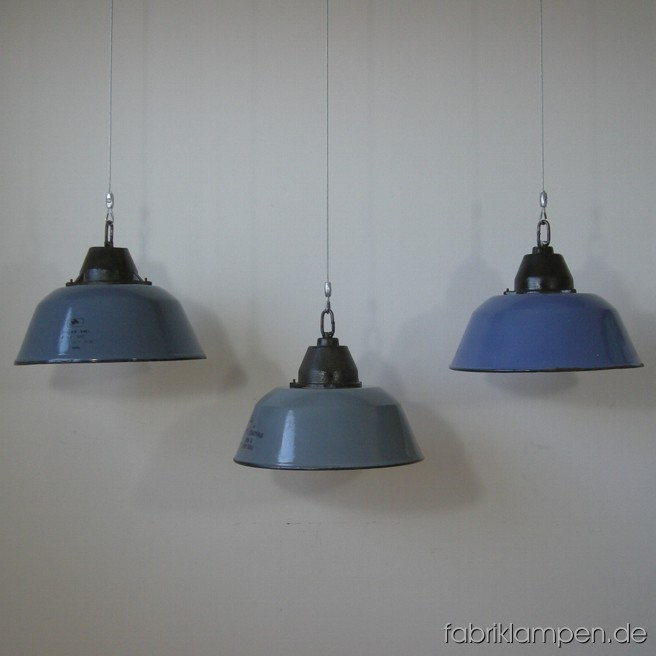 3 p. blue and gray enemeled industrial lamps with wire rope suspensions. Material: casted iron, enameled sheet with wire rope suspension. Without sockets – for the sockets there are a threaded tubes (M10) in the lamps, for 20 EUR additional price (pro lamp) we can electrify the lamps. Height of the lamp without wire rope mounting ca. 23 cm (9 inches), diameter ca. 36 cm (14,2 inches).