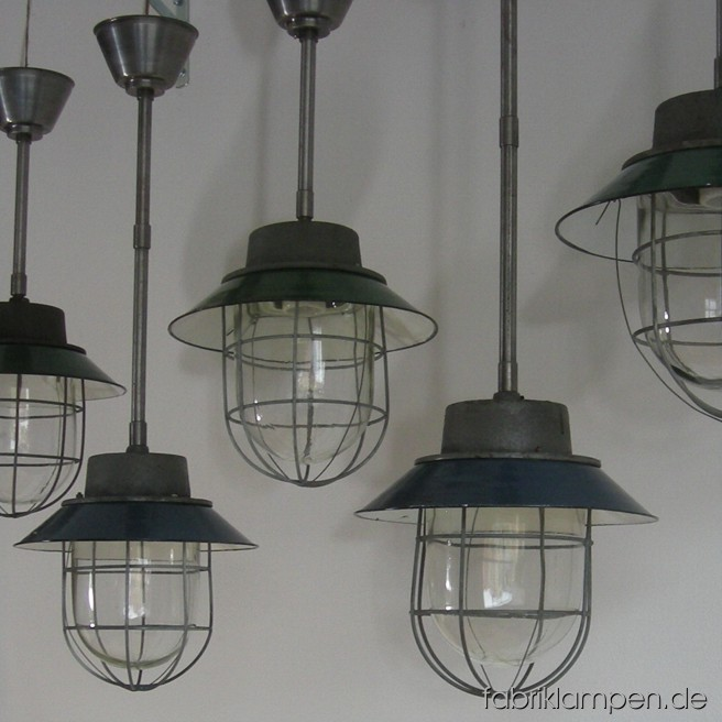 Industrial lamps with blue or green enamel shades and safety grids. Material: casted iron, steel, glass and blue or green enameled sheet. Newly electrified, with steel suspension. Height of the lamps ca. 30 cm (12 inches), diameter of the shades ca. 30 cm (12 inches), total height with suspension 63 oder 84 cm (25 – 33 inches).