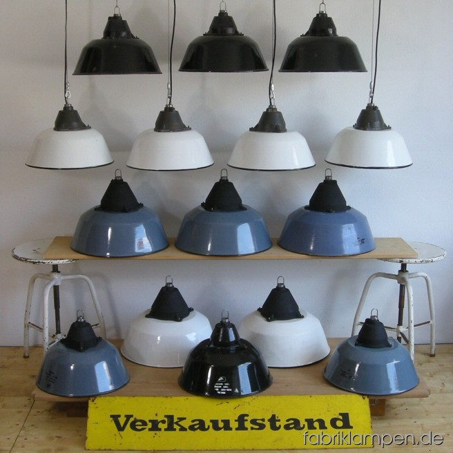 Industrial lamps in various colours and in two sizes. Material: white, gray (bluish) or black enameled sheet and casted iron, with wire rope suspension. Height lamps ca. 23 or 28 cm (9 or 11 inches), diameter of the lamps ca. 36 or 41 cm (14,2 or 16,1 inches).