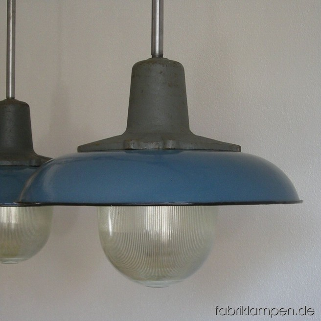 Industrial lamps with blue enamel shades and safety glasses. Material: casted iron, steel, glass and blue enameled sheet. Newly electrified, with steel suspension. Height of the lamps ca. 34 cm (13,4 inches), diameter of the shades ca. 42 cm (16,5 inches), total height with suspension 65 oder 86 cm (33,9 – 25,6 inches).