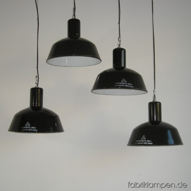 Black industrial lamps with enameled shades. Material: black enameled sheet. Newly electrified, with wire-rope suspension. Height of the lamps ca. 32 cm (12,6 inches), diameter of the shades ca. 41 cm (16,1 inches).