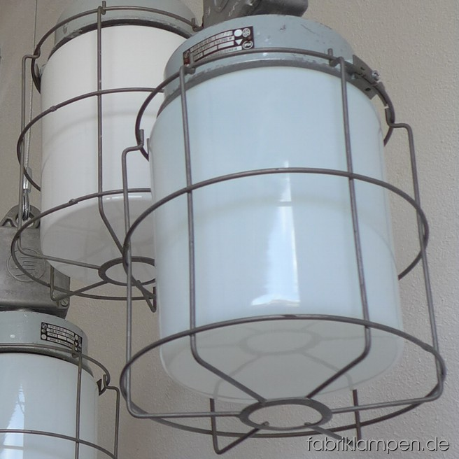 Gracile glass bulb lamps. Material: Aluminium dome and distribution box, stell grid, milk or opal glass. Newly electrified, with wire-rope suspension and textile cable. Height of the lamps ca. 40 cm (15,7 inches), diameter of the grid ca. 20 cm (7,9 inches).