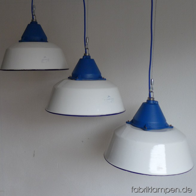 White industrial lamps. Material: white enameled sheet with blue dome and textile cable. Newly electrified, with wire-rope suspension. Height of the lamp is ca. 28 cm (11 inches), diameter of the shade is ca. 41 cm (16 inches). Other RAL-colors are possible too. We have also smaller specimens of this type on stock (diameter 36 cm – 14 inches).