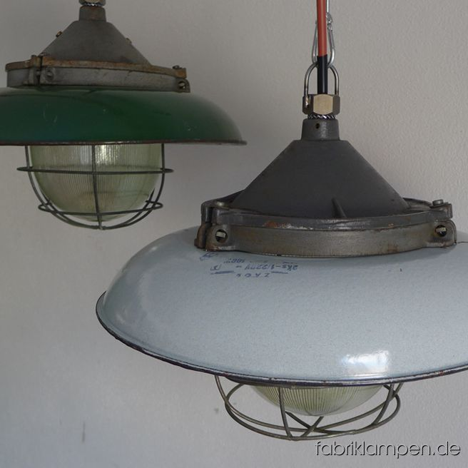 Old green and pale gray enamel industrial lamps with casted iron top. The lamps have the strong traces of usage and age. Material: casted iron dome, green or pale gray (inside white) enameled steel sheet, safety glass and grid. We have 9 pieces on stock. Height of the lamps ca. 30 cm (11,8 inches), diameter of the shades ca. 41 cm (16,1 inches).