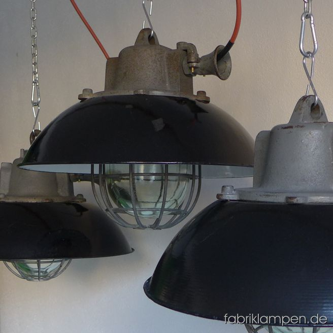 Very rare black enamel factory lamps with enamel shade and safety grid and glass. The lamps have the traces of usage and age. Material: casted iron top, black (inside white) enameled steel sheet. Cleaned, newly electrified, with E27 ceramic sockets. We have 10 pieces in stock. Height of the lamps ca. 33 cm (13 inches), diameter of the shades ca. 43 cm (17 inches).