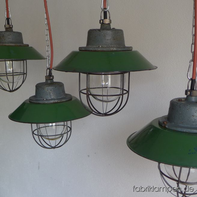 Old green enamel industrial lamp with enamel shade in green. The smaller version of these lamps. Material: casted iron dome, green enameled steel sheet (partly hallmarked),  safety glass and steel grid. We have various shades of colour (green) in stock. With traces of age and usage, cleaned and conserved. Newly electrified, with E27 porcelain bulbholders. Height of the lamps only ca. 24 cm (9,4 inches), diameter of the shades ca. 30 cm (12 inches).