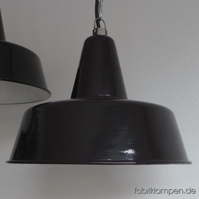 Rare old black factory lamps with hallmark (only one is hallmarked). These old industrial lamps have the traces of usage and age. Material: black (inside white) enameled steel sheet. Cleaned and newly electrified, with E27 ceramic bulbholders. Height of the lamps ca. 28 cm (11  inches), diameter of the shades ca. 40 cm (15,7 inches).