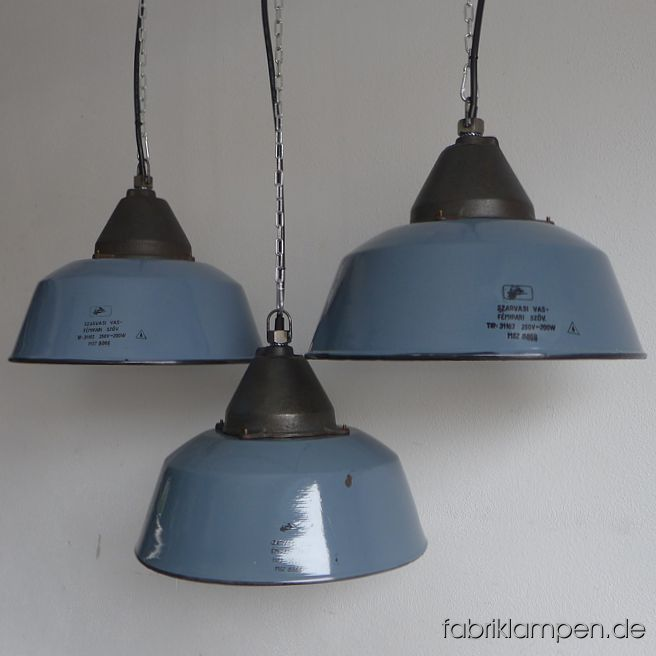 Nice old grayish blue enamel industrial lamps with casted iron top, hallmarked. The colour oft the enamel shades is ca. pigeon blue (RAL 5014). Material: grayish blue (inside white) enameled steel sheet, casted iron head. With traces of age and usage. Cleaned, newly electrified, with E27 ceramic sockets. Height of the lamps ca. 28 cm (11 inches), diameter of the shades ca. 41 cm (16,1 inches). The lamps will be shipped with 2 m cable and suspension eye (chain or steel-tube suspension is possible for an additional charge).