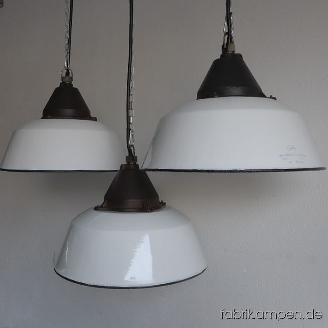 Nice old white enamel factory lamps with casted iron top, hallmarked. Material: white enameled steel sheet, casted iron head. With traces of age and usage. Cleaned, newly electrified, with E27 ceramic sockets. Height of the lamps ca. 28 cm (11 inches), diameter of the shades ca. 41 cm (16,1 inches). The lamps will be shipped with 2 m cable and suspension eye (chain or steel-tube suspension is possible for an additional charge).