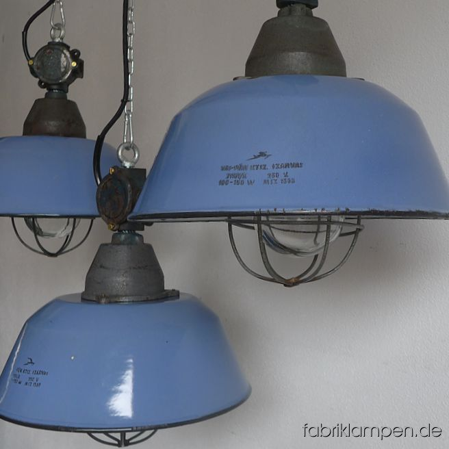 Nice old pale blue enamel factory lamps with casted iron top and distribution box, hallmarked. Material: rare pale blue (inside white) enameled steel sheet, casted iron head and distribution box, safety glass and steel grid. With traces of age and usage. Cleaned, newly electrified, with E27 ceramic sockets. Height of the lamps ca. 41 cm (16,1 inches), diameter of the shades ca. 36 cm (14,2 inches). The lamps will be shipped with 2 m cable and suspension eye (chain suspension is possible for an additional charge).