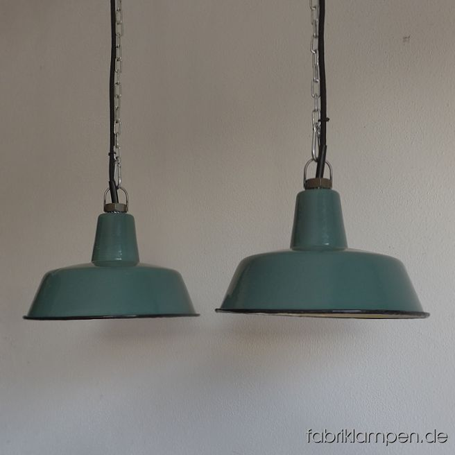 Nice old pale green enamel factory lamps. Material: rare pale green (inside white) enameled steel sheet. With traces of age and usage. Cleaned, newly electrified, with E27 ceramic sockets. Height of the lamps ca. 13 cm (5,1 inches), diameter of the shades ca. 25 cm (9,8 inches). The lamps will be shipped with 2 m cable and suspension eye (chain suspension is possible for an additional charge).
