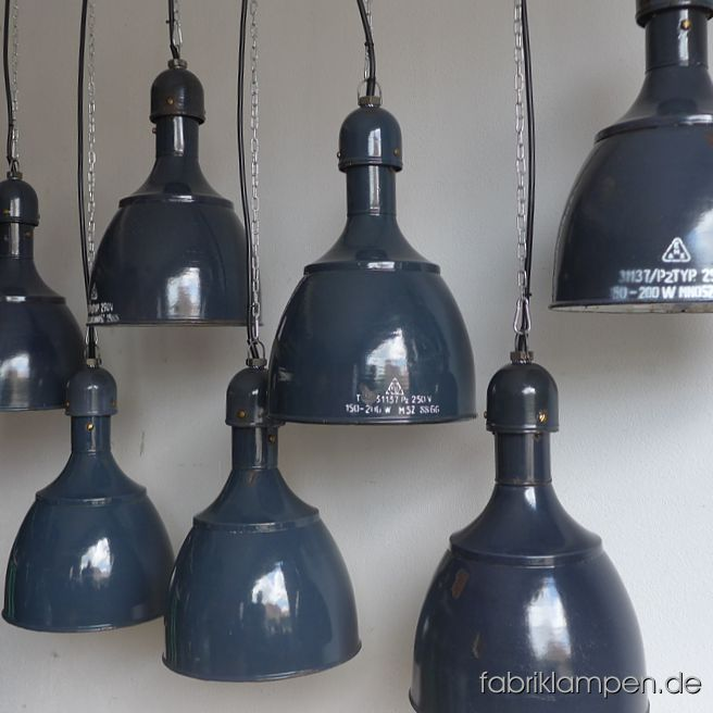 Old enamel industrial lamps in nice form, very rare. Hallmarked, the inscriptions are partly white, partly black (the black hallmarks are sometimes hardly to see). The lamps have strong traces of usage and age. Material: grayish blue (inside white) enameled steel sheet. Newly electrified, with E27 ceramic sockets. Height of the lamps ca. 46 cm (18,1 inches), diameter of the shades ca. 31 cm (12,2 inches). Please note: the form of these lamps is very popular and this form will be produced again in Eastern-Europe (and offered as originals in various colours). The cheap replicas are not difficult to identify. These lamps, as all of our lamps, are of course originals of their time.