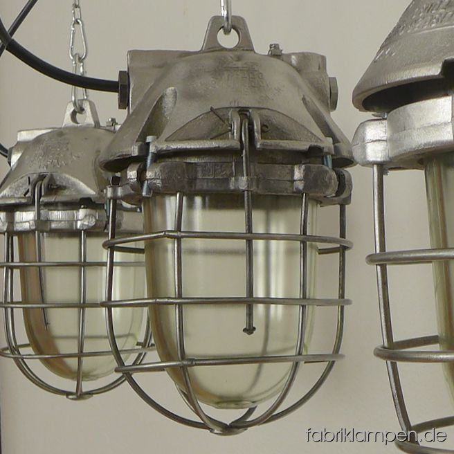 Rare smaller aluminium bunker lamp. Material: aluminium casing, safety glass and grid. Also in original condition in stock. Cleaned, preserved, newly electrified, with E27 sockets – we recommend LED bulbs for these lamps. Height of the lamps ca. 35 cm (13,8 inches), diameter of the lamps ca. 20 cm (7,9 inches). The lamps will be shipped with 2 m cable and suspension eye (chain suspension is possible for an additional charge).