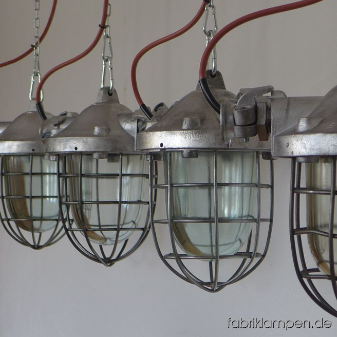 "Rare bigger aluminium factory lamps, bunker lamps. Material: aluminium casing, safety glass and grid. Cleaned, preserved, newly electrified, with E27 sockets – we recommend LED bulbs for these lamps. Height of the lamps ca. 35 cm (13,8 inches), diameter of the lamps ca. 20 cm (7,9 inches), maximum width with ""ears"" 32 cm (12,6 inches). The lamps will be shipped with 2 m cable and suspension eye (chain suspension is possible for an additional charge)."