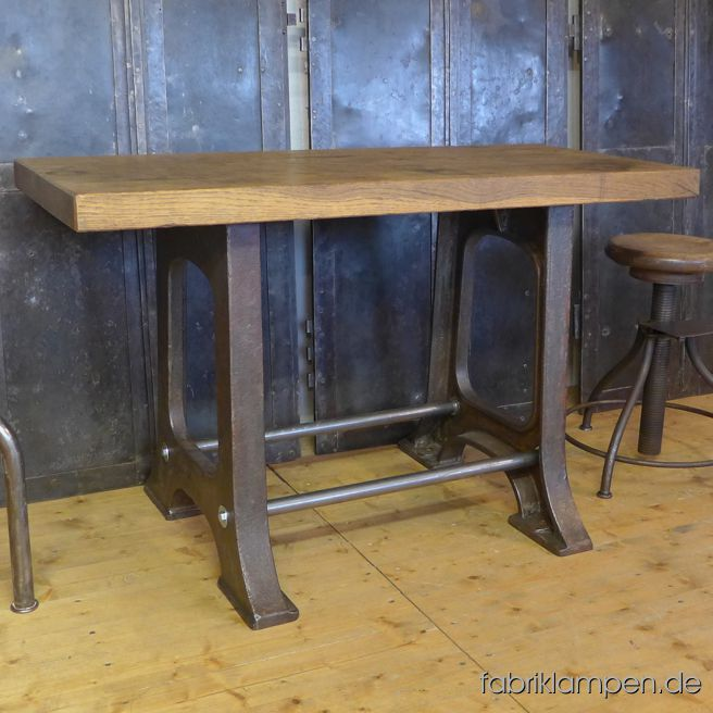 Old industrial table (workbench), restored. The casted iron pedestals are cleaned and waxed. Very fat and heavy tabletop (oak massiv, made of two pieces of wood) with nice traces of use on the surface. Perfectly cleaned and waxed. Height: 72 cm Tabletop: 119 cm x 54 cm x 5,5 cm (lenght x depth x thicknesss). Width of the pedestal at the bottom: 65 cm.