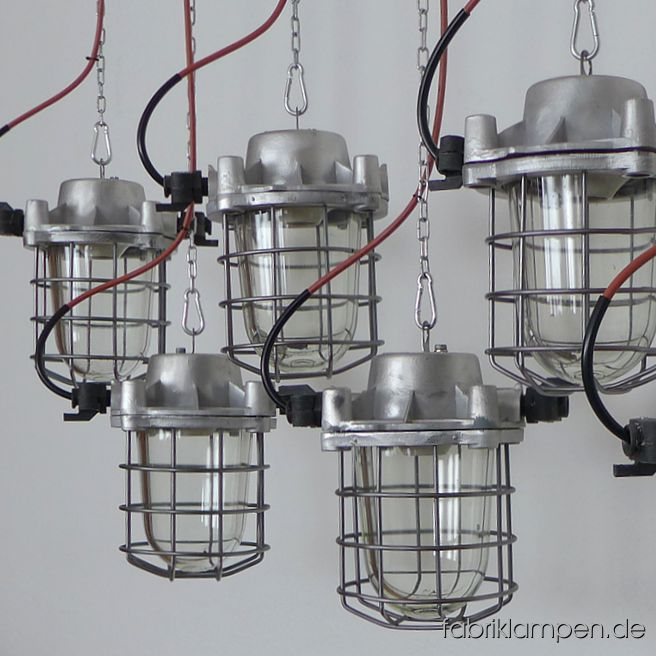 "Old bunker lamp. Material: aluminium casing, safety glass and grid. Also in original condition in stock. Cleaned, preserved, newly electrified, with E27 sockets – we recommend LED bulbs for these lamps. Height of the lamps ca. 30 cm (11,8 inches), diameter of the lamps (without ""ears"") ca. 20 cm (7,9 inches). The lamps will be shipped with 2 m cable and suspension eye (chain suspension is possible for an additional charge)."
