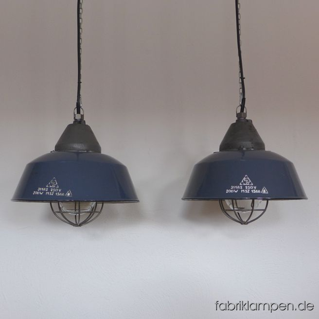 Old enamel industrial lamp with casted iron top and dark blue shade, hallmarked. Material: rare dark blue (inside white) enameled steel sheet, casted iron head, safety glass and steel grid. With light traces of age and usage. Cleaned, newly electrified, with E27 ceramic sockets. Height of the lamps ca. 36 cm (14 inches), diameter of the shades ca. 41 cm (16 inches). The lamps will be shipped with 2 m cable and suspension eye (chain suspension is possible for an additional charge).