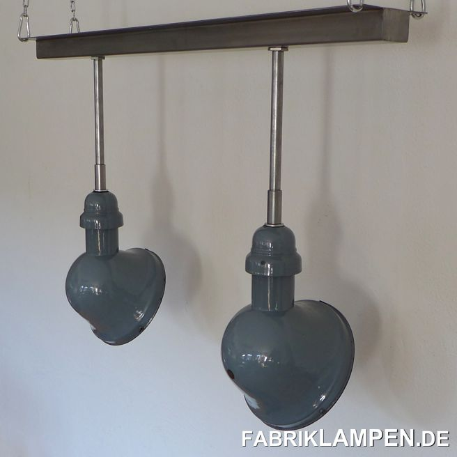 Asymmetric factory lamps with steel-tube suspension and rail. The old enamel shades have the traces of usage and age. Material: pale blue (inside white) enameled steel sheet. Cleaned and conserved, newly electrified, with E27 ceramic sockets. Suspension: steel-tube suspension and rail. Diameter of the shade is ca. 22 cm (8,7 inches), total height of the lamps is 64 cm (25,2 inches), lenght oft he rail is 96 cm (37,8 inches). Longer suspension is possible.