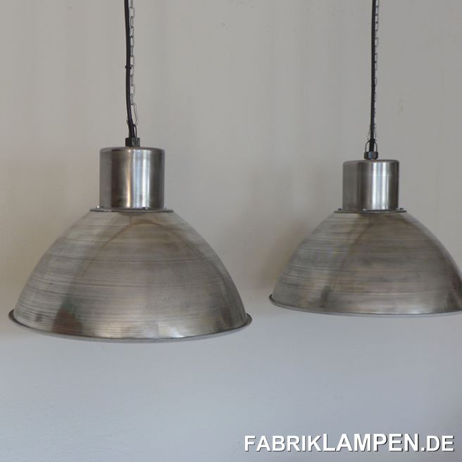 Old aluminum industrial lamps, polished. These large old factory lamps are polished and the shade is painted white on the inside. The lamps are newly electrified, with E27 ceramic socket.Material: polished steel top, polished aluminum shade (careful, so the patina of the old shades can still be felt). The surface of the shades is grooved.You get these factory lamps with hanging eyes and 2 meters of cable (other lengths are of course possible). On request, the lights can be equipped with textile cables and chain suspension (for an additional charge).Lamp diameter 51 cm, height approx. 39 cm (without eyelet).The lamps are also suitable for rooms with a lower interior height.