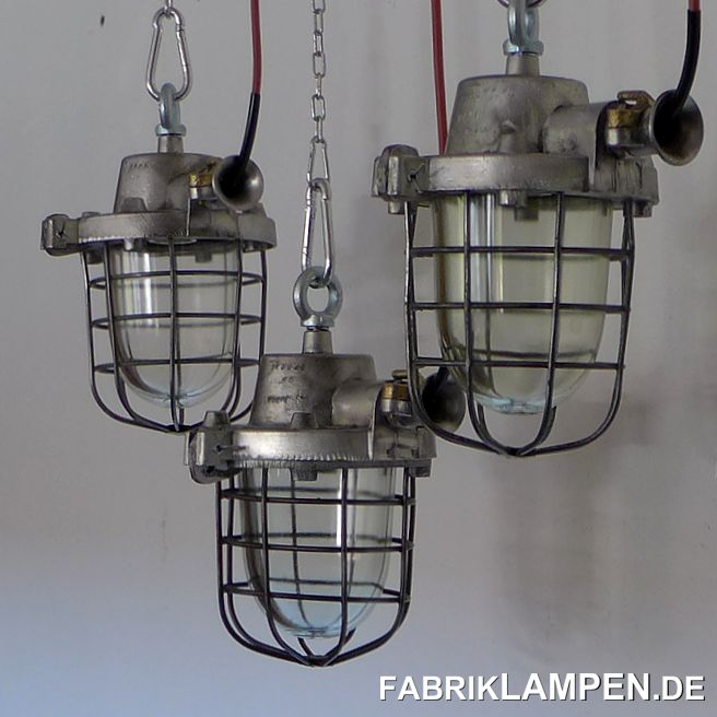 Old industrial lamp (bunker lamp), aluminum, with safety glass and grid. The lamps are restored.The lamps have been cleaned, restored and newly electrified (with new E27 ceramic sockets). Material: casing made of aluminum, safe grid made of steel, safety glass (thermo glass). The clamp part on the ear is made of brass, which is rather rare and gives the lamps a special charm.The dimensions: height of the lamps (without hanging eye) 30 cm (11,8 inches), diameter of the housing (without