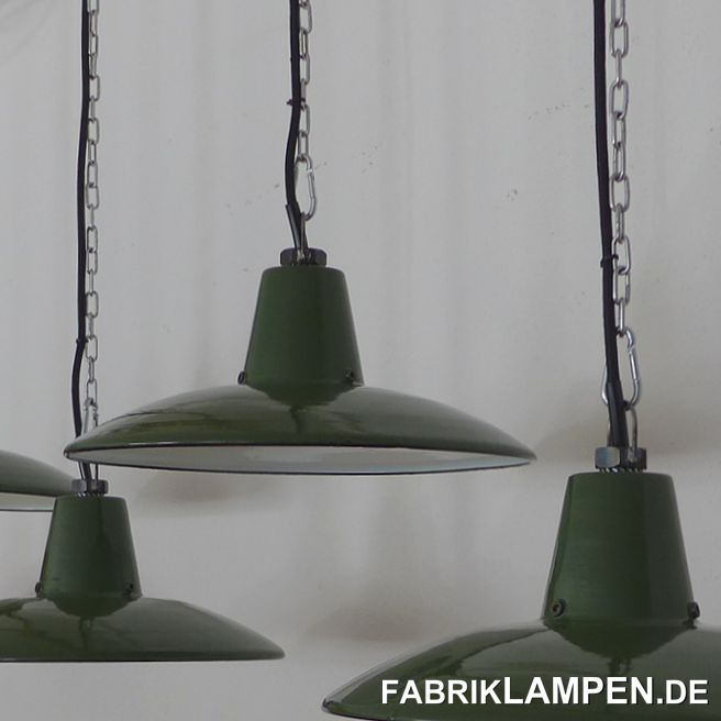 Green factory lamps, old enamel, from old stock. Perfectly preserved old lamps from the 1950s. Since the term old stock really means a lot of things nowadays that simply have nothing to do with the term old, we took some pictures of the lamps as they were found (last picture in the gallery). The lamps were part of a larger find, which is extremely rare from this time. You can find more details here. Since this batch also included shades from Louis Poulsen in two dimensions and in larger numbers, it cannot be ruled out that these lamps could also come from Louis Poulsen.The lamps have a very clear and minimalist shape of the 1950s.These old industrial lamps were never in use and therefore in very good condition. Here and there - simply because of their age - they have slight traces of the past decades (small chips, rust spots, discolorations, etc.).They are cleaned and newly electrified, with new E27 ceramic sockets.Material: green (white inside) enameled steel sheet. At the bottom of the neck are 3 threaded holes, probably for attaching a glass. Most of the enamel industrial lamps, which can also be used with glass, were used without glass, even with these shades there is no glass.You get the lamps with 2 meters of textile cable in the color of your choice and a massive hanging eye for safe hanging. The lamps can also be supplied with chain or tubular steel suspension for an additional charge. We can also offer canopies.The dimensions: height of the lamps approx. 14 cm (without eyelet), diameter approx. 34.5 cm.
