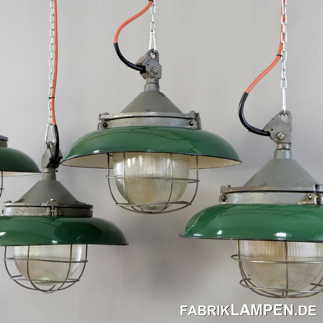 Old green industrial lamp with enamel shade. A classic bunker lamp made with a shade. These lamps exist in two colours: light grey and green. We have both versions in stock. Material: green (inside white) enamelled sheet steel, cast iron housing, protective glass and steel grid. The lamps have the traces of the past decades (discolourations, small chips, rust spots and so on - we have treated them all). The headboards have been refurbished. The old industrial lamps have been restored: cleaned and conserved. The factory lamps are newly electrified, with new E27 ceramic sockets, the complete interior is new.Your old industrial lamp will be delivered with 2 metres of cable (other lengths are of course possible) and with the original, massive suspension eye for safe hanging. For an extra charge, the factory lamps can also be supplied with chain suspension. We can also offer canopies.Old green industrial lamp, the dimensions: Diameter lamp (shade) 41 cm, height 30 cm.